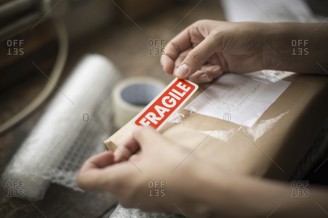Hands holding a red Fragile sticker to stick it on a brown paper package on a work bench