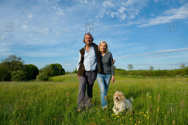 Man and woman walking arm in arm across a meadow, small dog running beside them