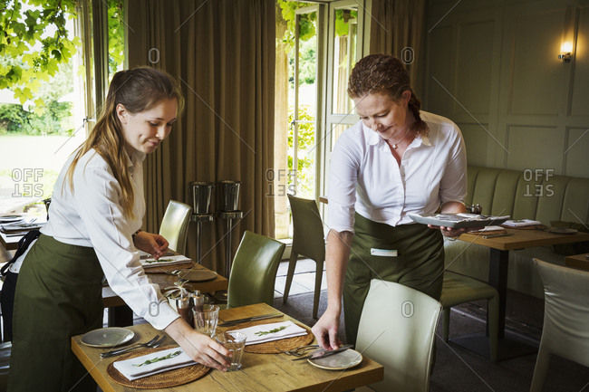 Two women wearing aprons setting tables in a restaurant