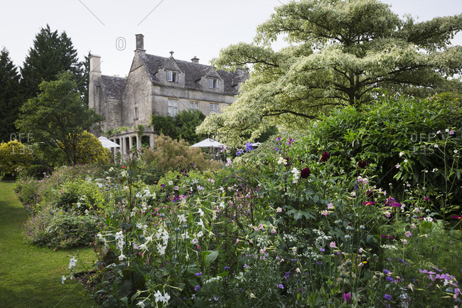 Exterior view of a 17th century country house from a garden with flower beds, shrubs and trees
