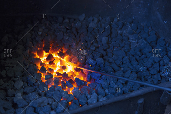 A glowing metal rod in the hot coals in a blacksmith's forge