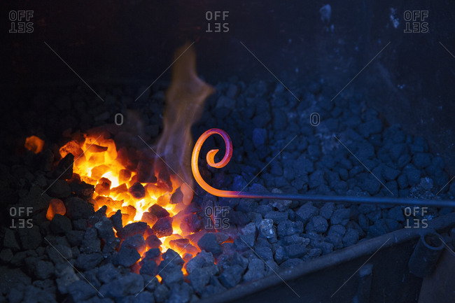 Close up of glowing metal rod with a scrolled end, held over hot coals in a blacksmith's workshop