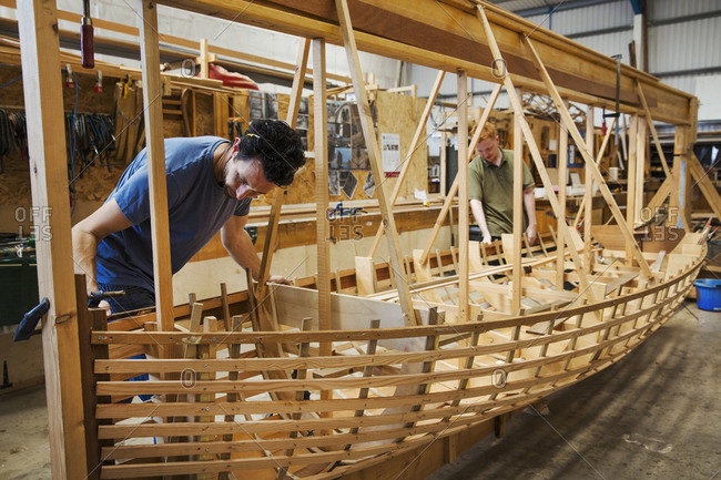 Two men in a boat-builder's workshop, working together on a wooden boat hull