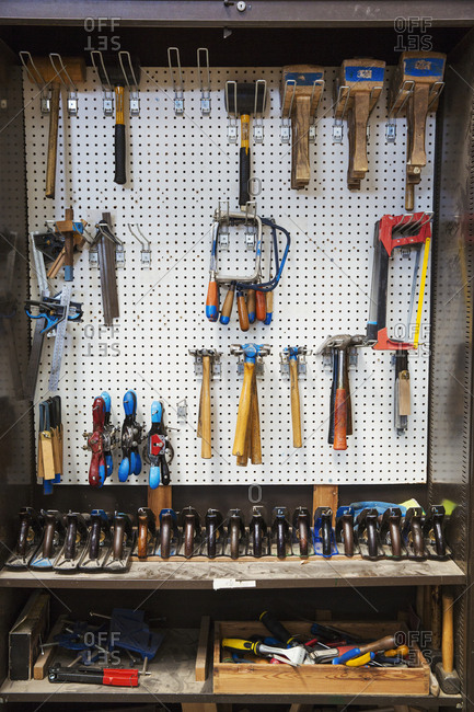 Work bench in a boat-builder's workshop, selection of hand tools for wood working hanging on a wall