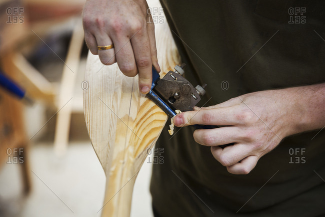 Close up of person working in a boat-builder's workshop, working on a wooden oar