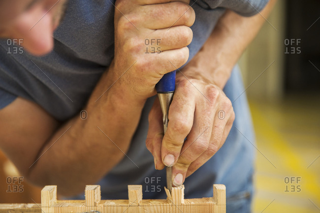 Close up of man working a boat-builder's workshop, joining together two pieces of wood