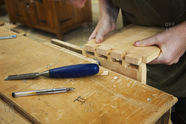 Close up of person working a boat-builder's workshop, joining together two pieces of wood