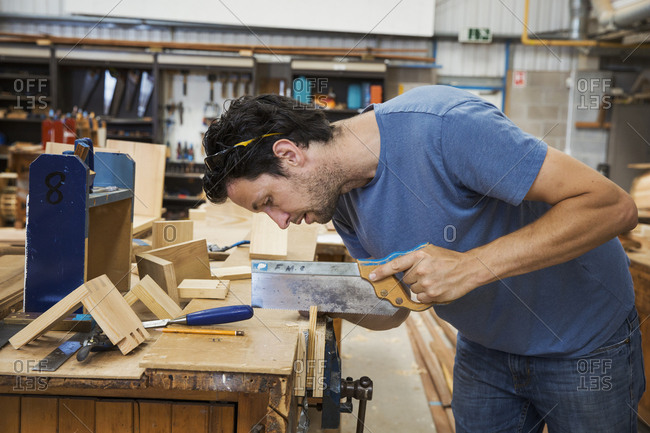 Man working a boat-builder's workshop, sawing small piece of wood with hand saw