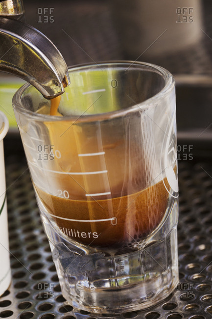 Close up of fresh brewed espresso coffee pouring into a glass from a coffee machine