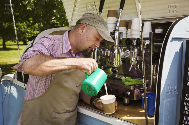 Bearded man wearing apron standing by blue mobile coffee shop, making coffee