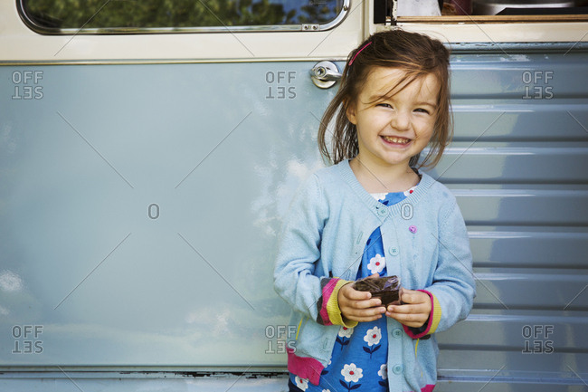 Smiling girl standing in front of blue mobile coffee shop, holding chocolate brownie
