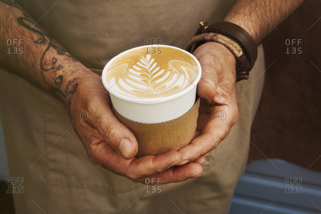 Close up of man with tattoo on his arm holding paper cup with cafe latte