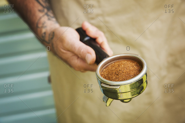 Close up of man with tattoo on his arm holding portafilter for espresso machine