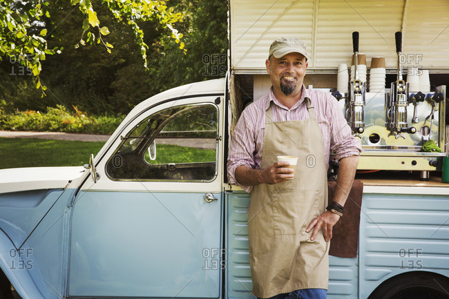 Bearded man wearing apron standing by blue mobile coffee shop, holding hot drink, smiling at camera
