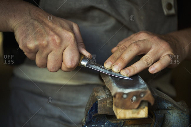 Close up of a wood carver honing the blade of a carver's knife on a leather strop, pressing the blade down, sharpening his tools