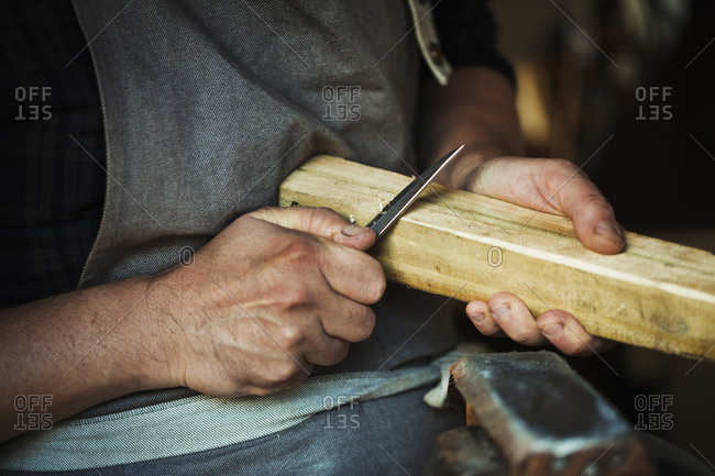 Close up of a craftsman cutting and paring the corners of a piece of wood with a sharp carving knife