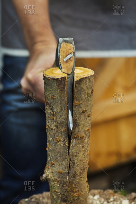 A wood carver splitting small log of wood in half with an axe