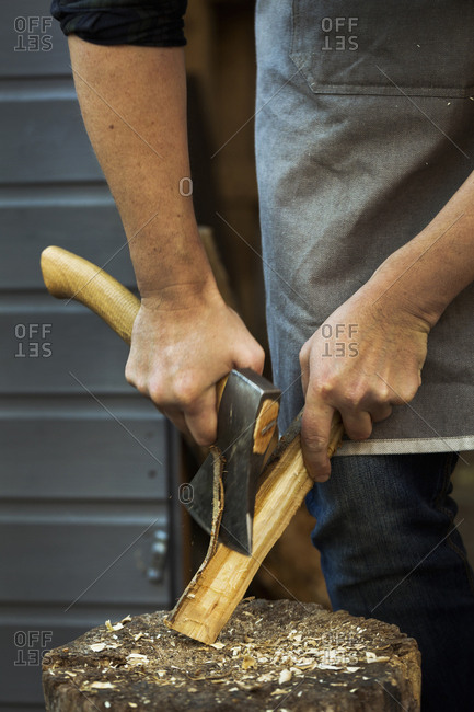 A craftsman holding a small axe, cutting down a small piece of wood on splitting block covered in wood shavings