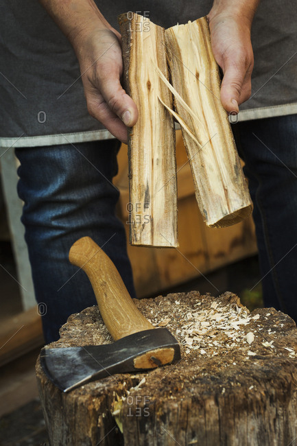 Close up of a person holding small log of wood split in half and a hand axe resting on a splitting block