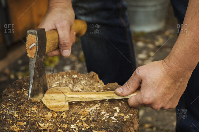 Close up of person holding a hand axe, cutting and shaping a small piece of wood on a splitting block covered in wood shavings