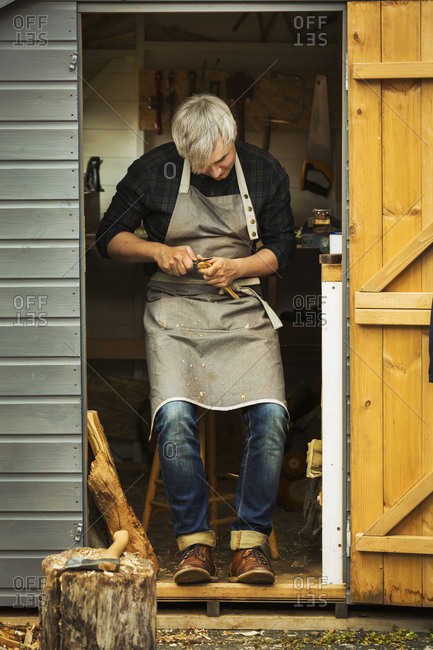 A craftsman wearing a hessian apron sitting in the doorway of a workshop, carving a small piece of wood