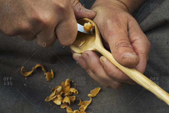 A craftsman carving wood, shaping the bowl of a hand carved wooden spoon with a sharp handheld tool