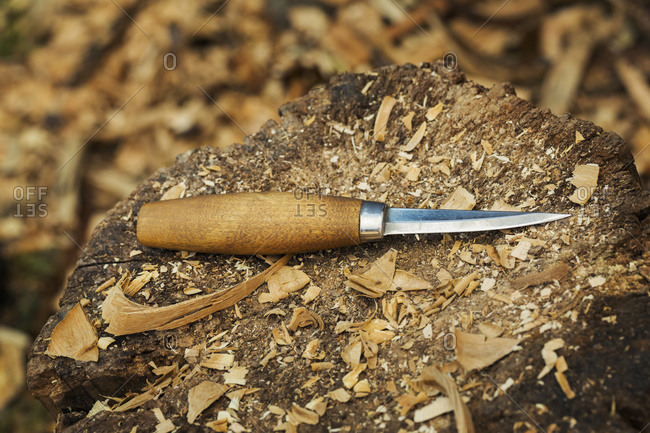 A carving knife with wooden handle lying on splitting block covered in wood shavings