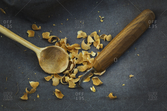Close up of a handmade hand carved wooden spoon with round bowl end, a sharp carver's knife and wood shavings