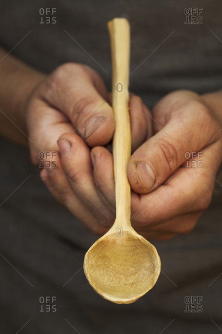 A man's hands holding a handcrafted hand made wooden spoon with a long slender handle and round polished bowl