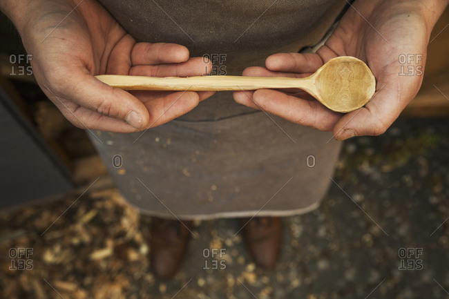 A man's hands holding a hand carved wooden spoon with a long tapering handle and smooth round bowl end