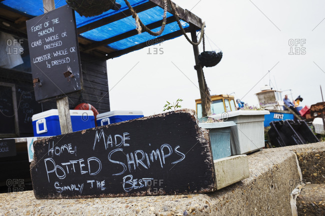 Handwritten sign advertising home made potted shrimp outside a fish shop in a Suffolk harbor