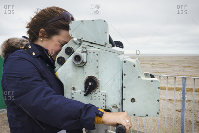 Side view of woman standing on the coast, looking through coin operated binoculars
