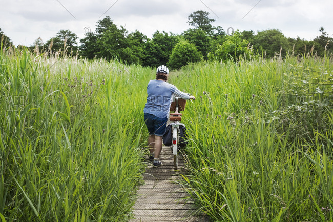 Rear view of woman pushing bicycle along path through tall grass
