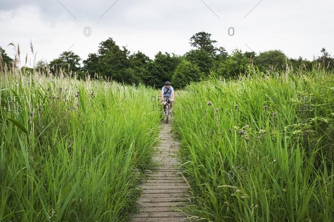 Woman cycling along path through tall grass