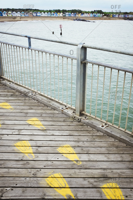 Yellow footprints on a traditional wooden pier in a coastal town