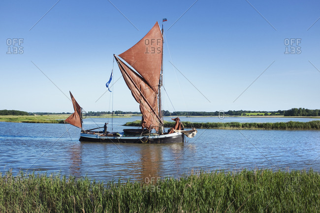 Traditional sailing boat with red sails and a gaff rig, a sailing smack on the water on a reed bed or river estuary