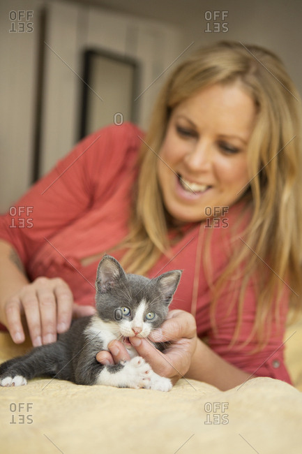 A woman with a small grey and white kitten