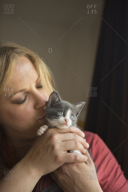 Woman holding a small grey and white kitten in her two hands, nuzzling it