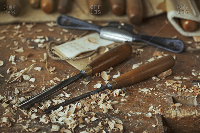 Close up of wood carving hand tools, chisels and wood shavings on a bench in a carver's workshop
