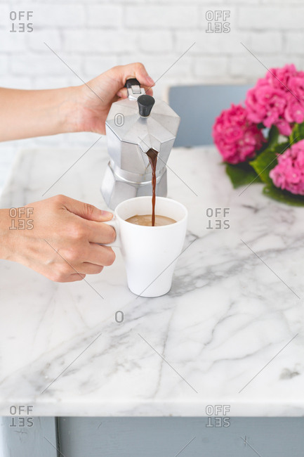 Woman pours coffee from a moka pot