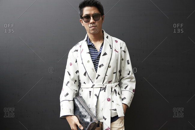 London, England - June 9, 2017: Asian man wearing short dressing gown and holding sponge bag against black wall in the street during London Fashion Week Men's
