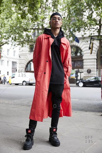 London, England - June 9, 2017: Man wearing long red coat over black clothes poses for the camera in the street during London Fashion Week Men's