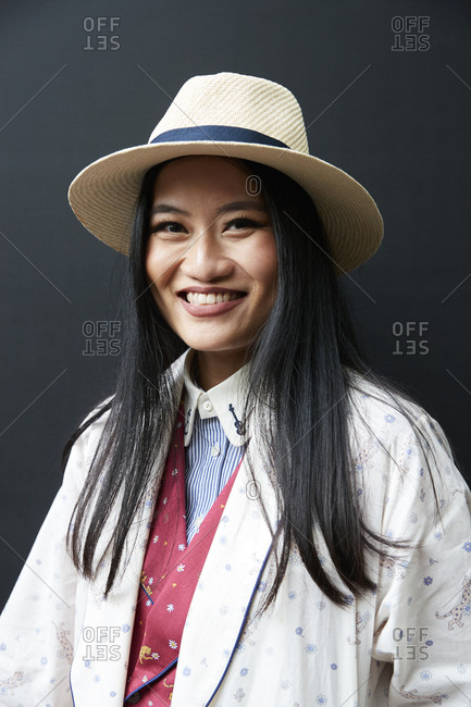 London, England - June 9, 2017: Smiling Asian woman wearing pajama suit, robe, shirt and Panama hat against black wall in the street during London Fashion Week Men's