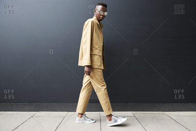 London, England - June 9, 2017: Young black man wearing a beige suit and trainers walking against black wall in the street during London Fashion Week Men's