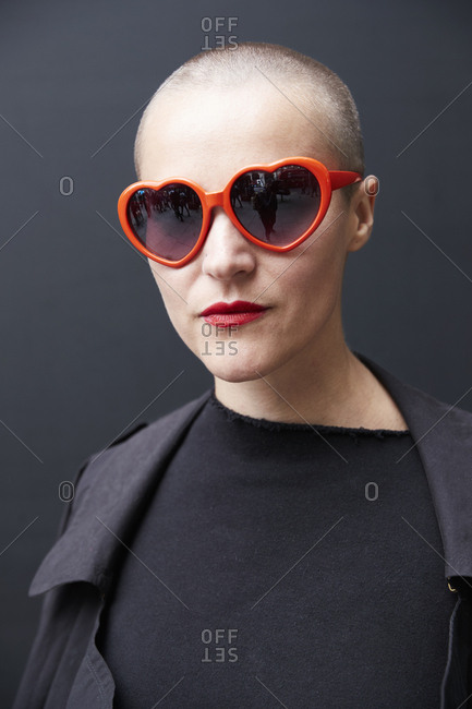 London, England - June 9, 2017: White woman with a shaved head wearing red heart-shaped sunglasses and red lipstick against a black wall in the street during London Fashion Week Men's