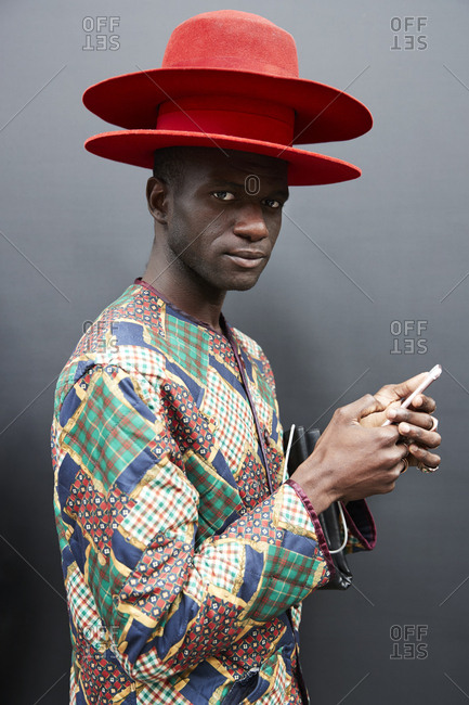 London, England - June 9, 2017: Black man wearing two red hats standing against black wall during London Fashion Week Men's