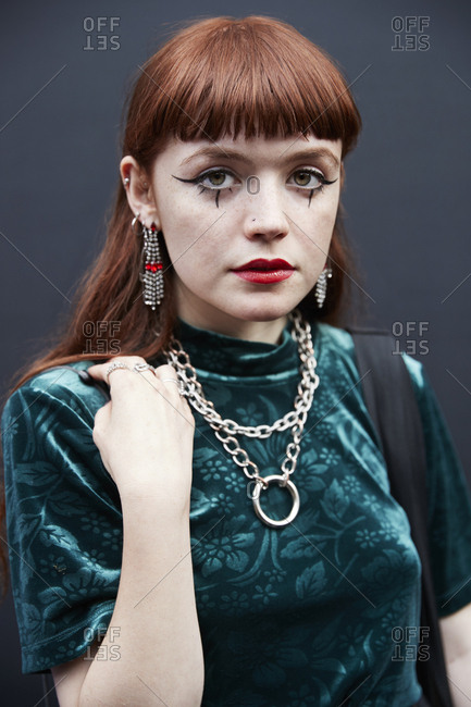 London, England - June 9, 2017: Young white woman with long red hair and fringe wearing green velvet top against a black wall at London Fashion Week Men's