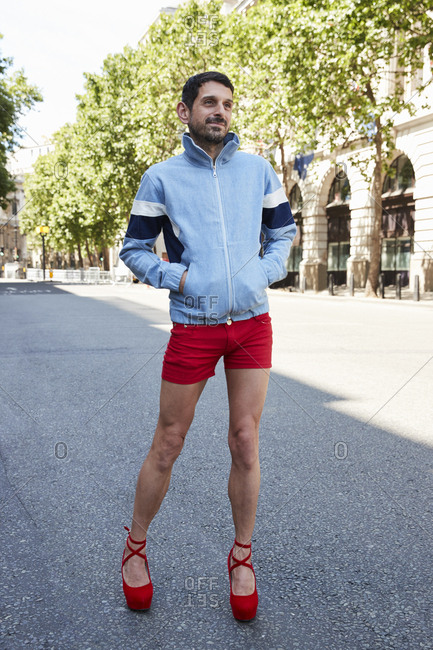 London, England - June 11, 2017: Bearded white man wearing red shorts and red high heels in the street during London Fashion Week Men's