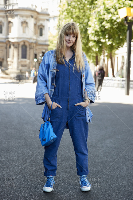 London, England - June 11, 2017: White woman with long blonde hair wearing denim jumpsuit and jacket standing in the street London Fashion Week Men's