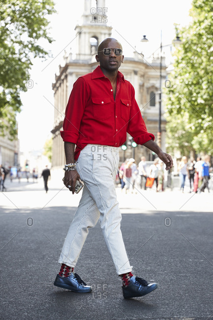 London, England - June 11, 2017: Black man wearing red shirt, pale striped trousers and sunglasses walking in the street during London Fashion Week Men's